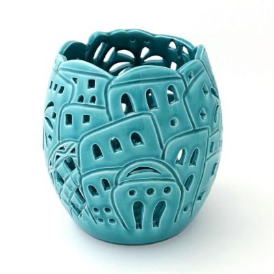 Handmade green-turquoise open ceramic candle holder carved with oblique village scene